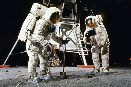 Buzz Aldrin and Neil Armstrong in training for the Apollo 11 mission. Aldrin scoops up a soil sample, while Armstrong aims his camera. Photo by NASA.