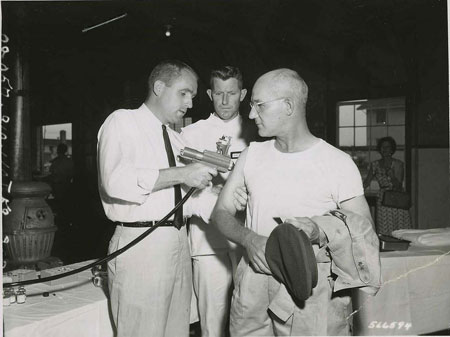 SP5 Lawrence E. Blackman (Darlington, SC) Hq & Hq Co, USASTC, receives the first typhus shot administered by Hypospray Jet Injector at Fort Gordon. 08/26/1959. Photo by Roy C. McManus